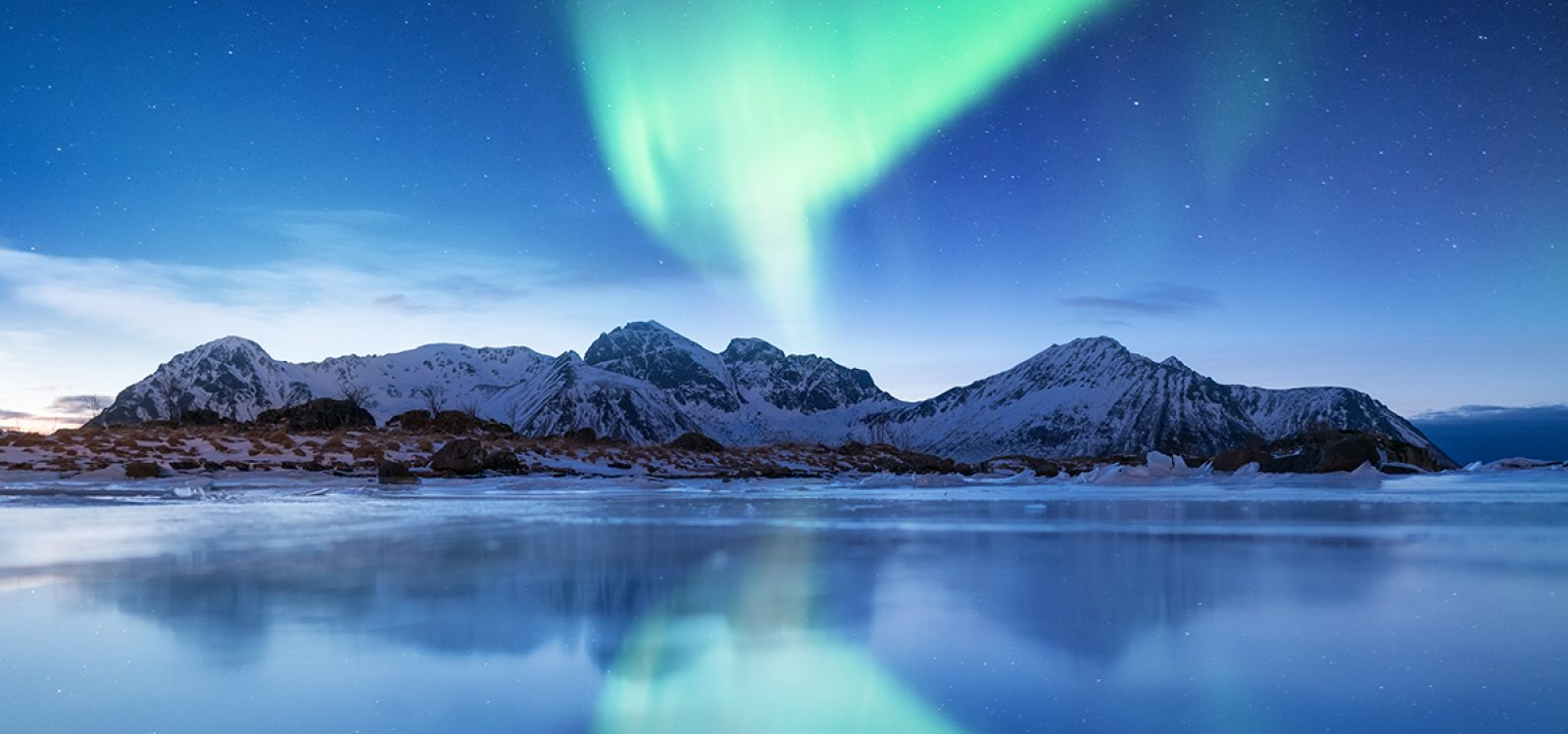 Aurora borealis on the Lofoten islands, Norway. Green northern lights. Night sky with polar lights. Night winter landscape with aurora and reflection on the ice surface. Natural background in the Norway