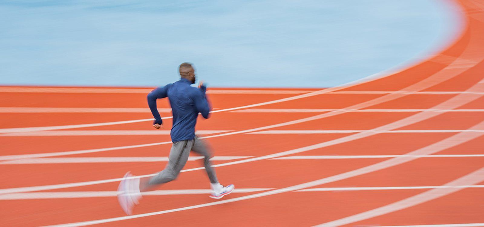 Young African American man running at tartan.